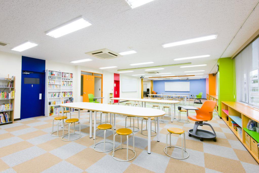 壁で区切られていない、オレンジ・ベージュ・グリーン・ブラウンカラーのカーペットで仕切られた4つのゾーンが隣接。